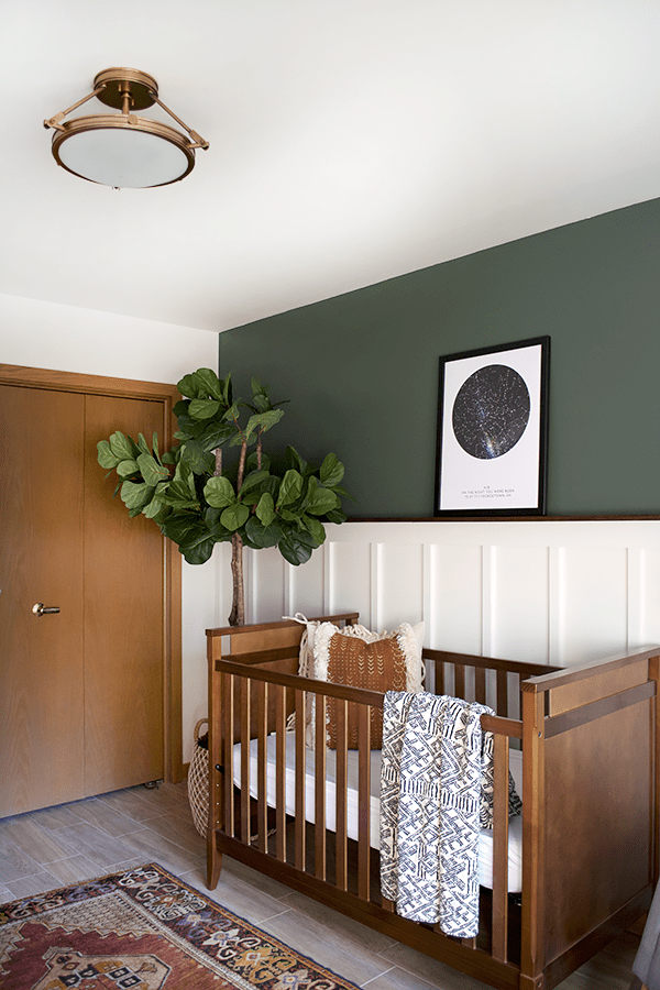 earthy rustic nursery room dark wood baby crib boho styled area rug white wainscoting wall woodland green wall houseplant