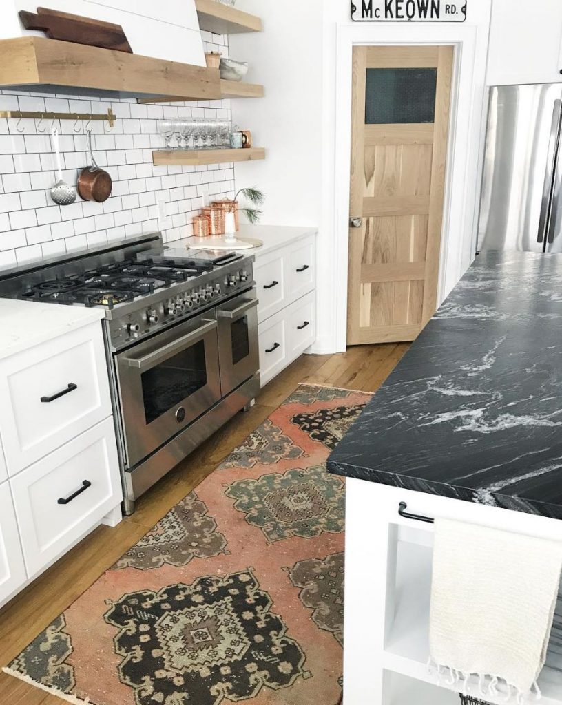 honed granite kitchen countertop in black white kitchen countertop stainless steel kitchen appliances wooden open shelves wood floors shabbier runner rug