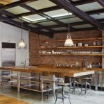 Industrial Kitchen With Rustic Open Shelves Blockbutcher Island Red Brick Walls Pipe Legs Stools Stainless Steel Appliances