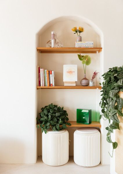 minimalist reading nook recessed bookshelves a pair of white stools some greeneries