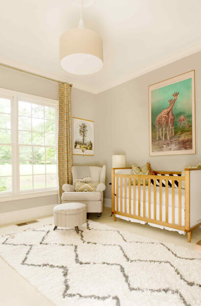 nursery room idea animal themed artwork wooden baby crib white nursery chair white round table wooly area rug with dark line accent