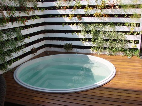 rounded in ground hot tub idea white painted wood panel walls with growing vines & greenery