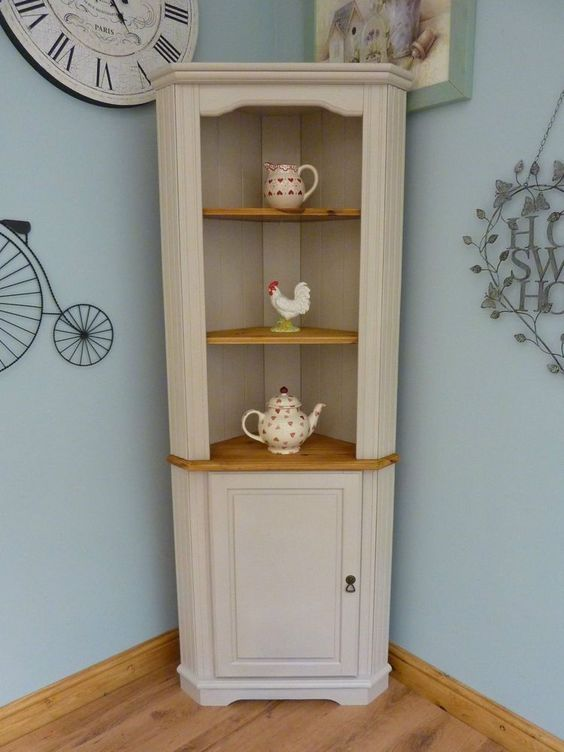shabby chic corner cabinet in white and supported with wood trays for antiques