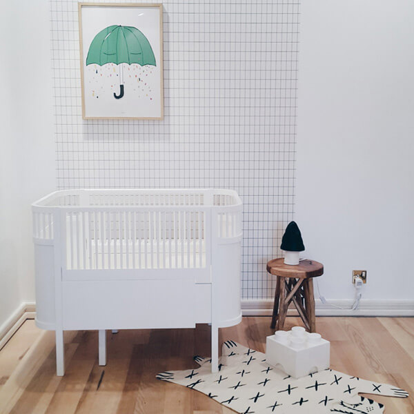 simple nursery room idea simply striped wallpaper in white white baby crib light wood floors animal themed mat simple wood side tabel with round top