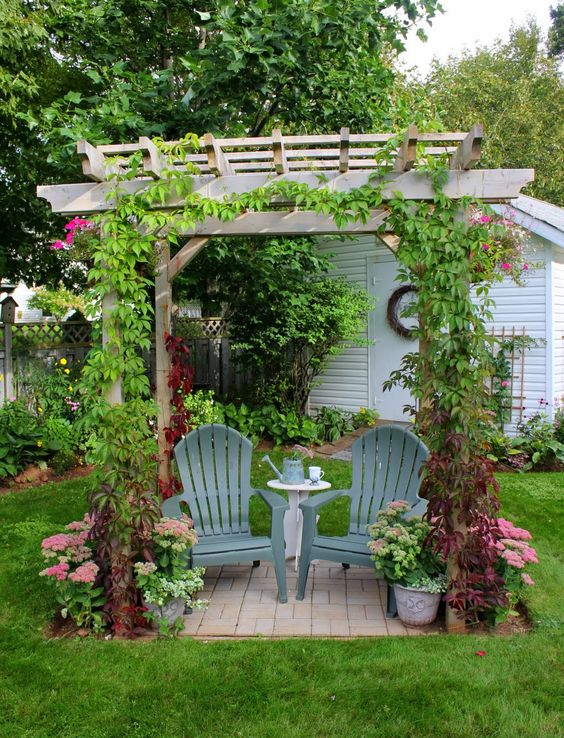 small pergola as garden nook a pair of wood chairs small side table in white climbers potted plants