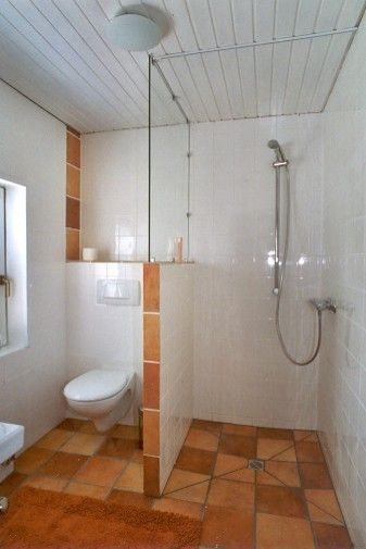 two chamber bathroom design terraccotta floorings white ceramic walls ceramic clear glass divider wall mounted toilet in white walk in shower