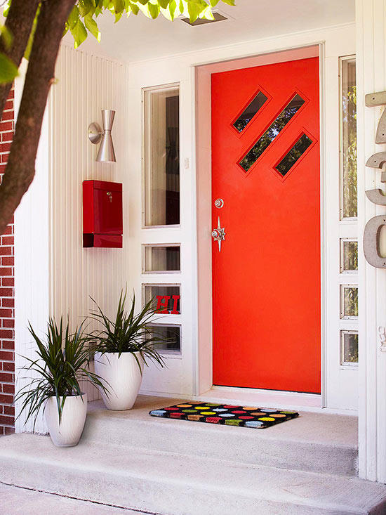 vividly bright orange front door with star doorknob colorful polka dot doormat red mailbox