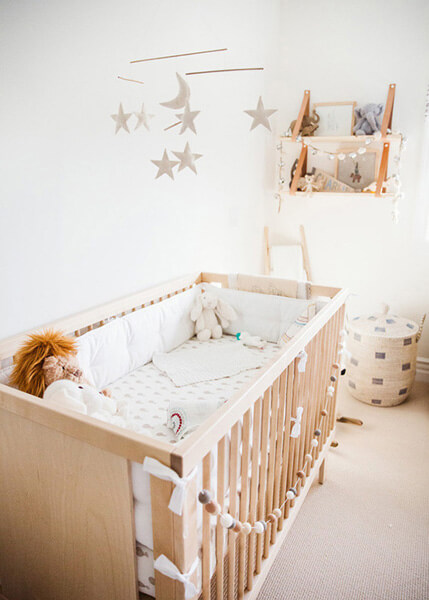 wooden baby crib with animal stuffs open shelves made of wood with animal stuffs hanging decorative stars and moon