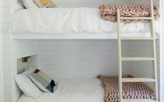 Nordic inspired bedroom for kids pale wood ladder and floors white siding walls and ceilings white bedding treatment woven wool blankets