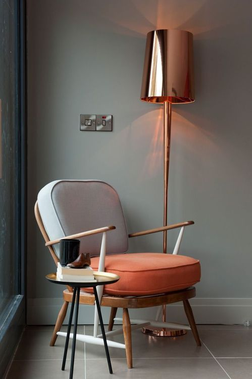 angled legs modern chair with neutral upholstery minimalist floor lamp with copper lampshade