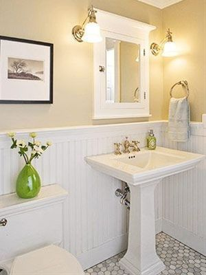 clean classic and practical bathroom white pedestal sink light cream walls white pallet wainscotings hexagon mosaic tiles floors warm lighted sconces