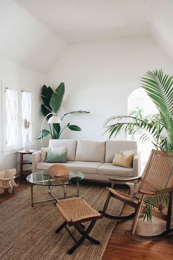 coastal themed living room in neutral tone soft neutral sofa woven area rug woven side table woven rocking chair medium size tropical houseplants