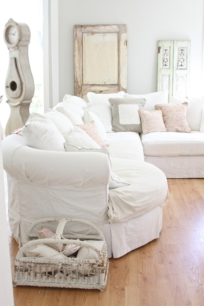 cottage themed living room in neutral palettes light wood floors old window shutter decorations white slipcovers with throw pillows