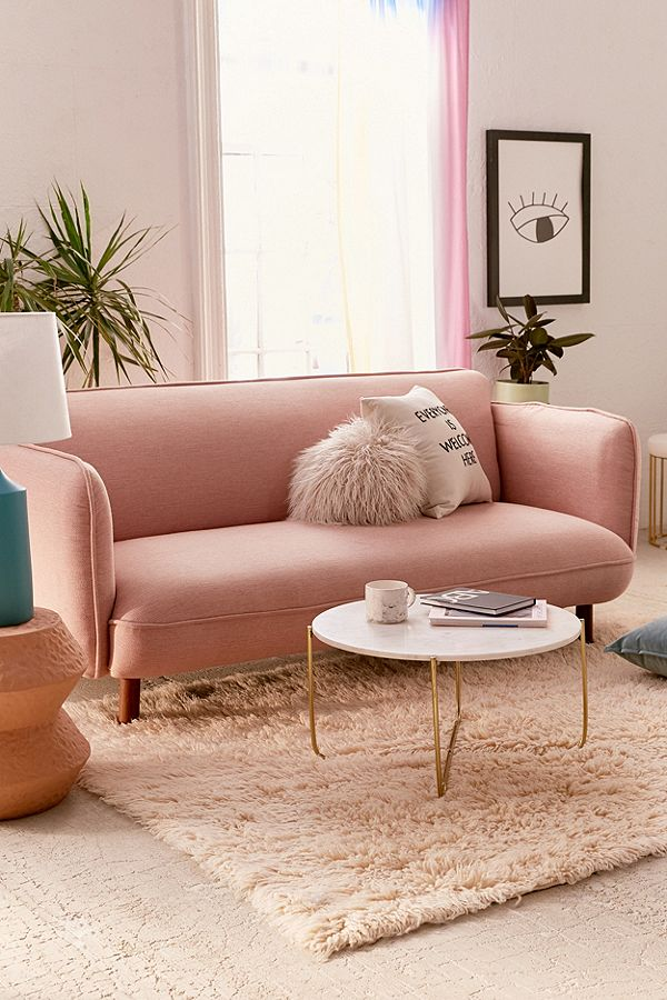 dainty pink upholstered sofa with cylindrical wood legs light pink wooly rug white round top coffee table with gold toned tiny metal legs