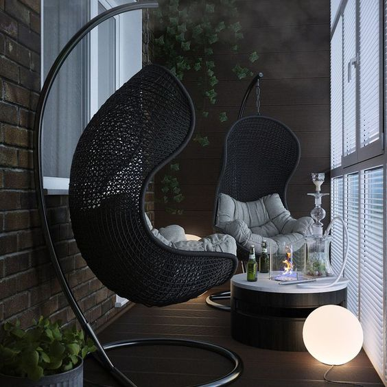 dark toned balcony with screen matte black hang chairs with futons round top coffee table floor bulb fixture