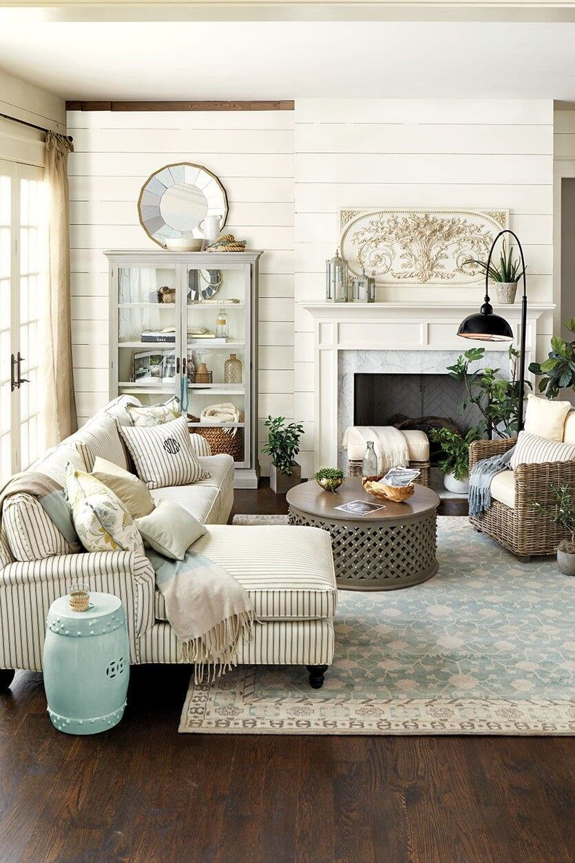 farmhouse living room with rustic touch striped couch with additional facing chaise patterned area rug round top coffee table dark wood floors shiplap walls in white display cabinet with glass door