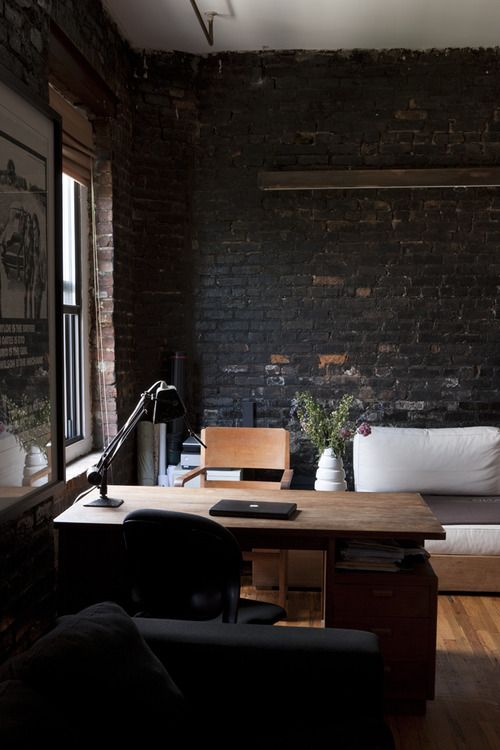 formal home office in living room modern white sofa heavy wood working desk black brick walls wood floors