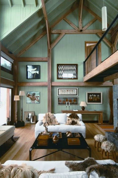 grand rustic farmhouse living room blue wood siding walls hardwood beams and structure supports wood floors white sofa black coffee table