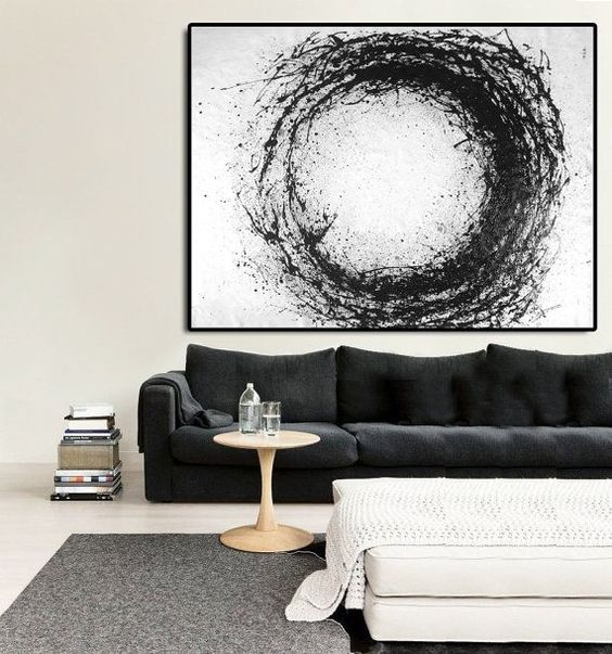 modern black white living room black sofa round top coffee table in light wood material gray area rug modern circle art in black and white
