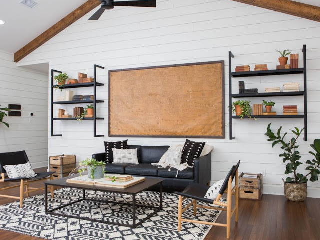 modern farmhouse living room black leather sofa black coffee table monochromatic area rug industrial style wall racks decorative wall board dark wood floors white siding interior walls