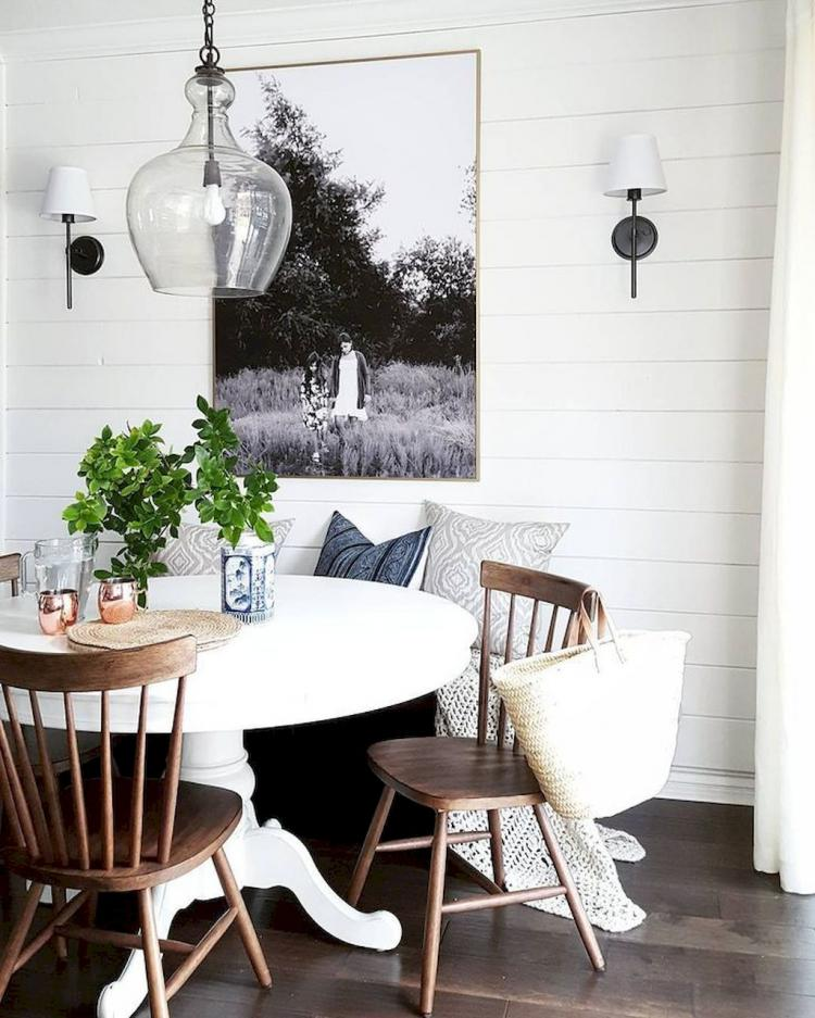 modern rustic breakfast nook white round top dining table wooden dining chairs white wood siding walls wood floors pendant with glass lampshade a couple of wall sconces