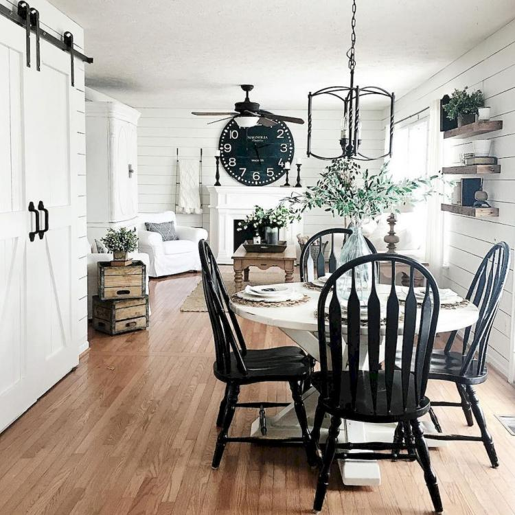 modern rustic dining room black painted dining chairs white round top dining table wood floors white wood siding walls black giant clock