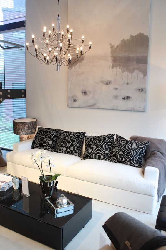 muted black white living room warmer look chandelier white sofa patterned black throw pillows modern black coffee table great abstract art