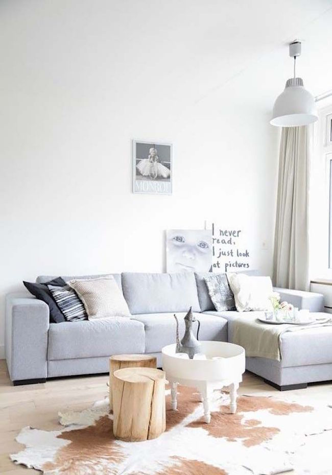 neutral palette living room soft blue couch with facing chaise addition cowhide rug log side tables small round top center table light wood floors