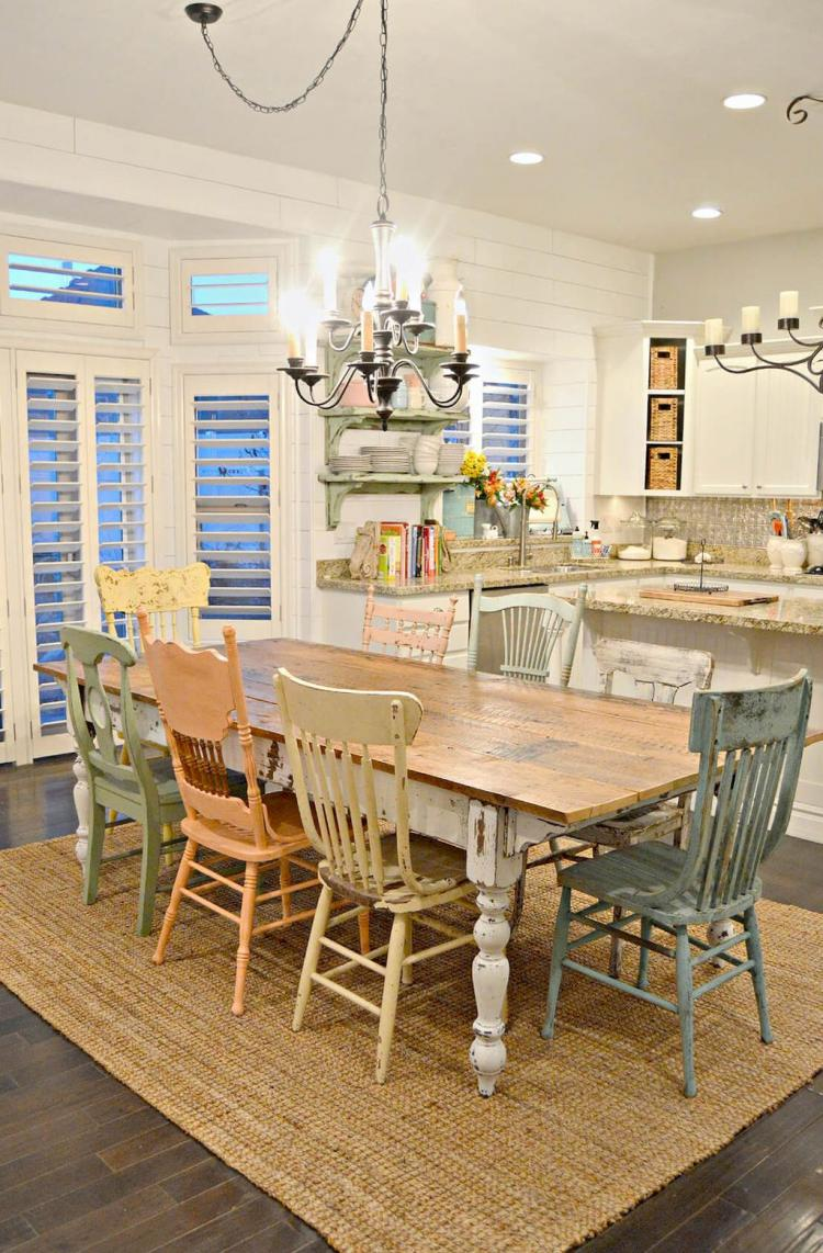 rustic dining room woven natural fiber rug mismatching dining chairs wooden dining table traditional chandelier