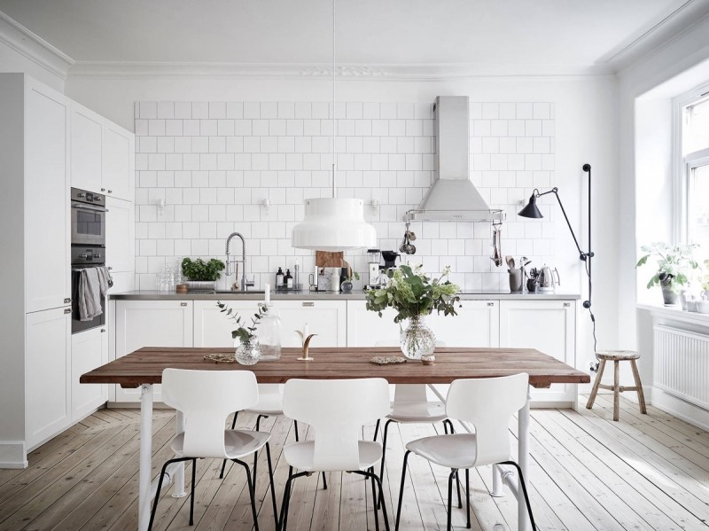 scandinavian kitchen design block butcher dining table modern white dining chairs white subway ceramic tile walls white cabinetry light wood floors