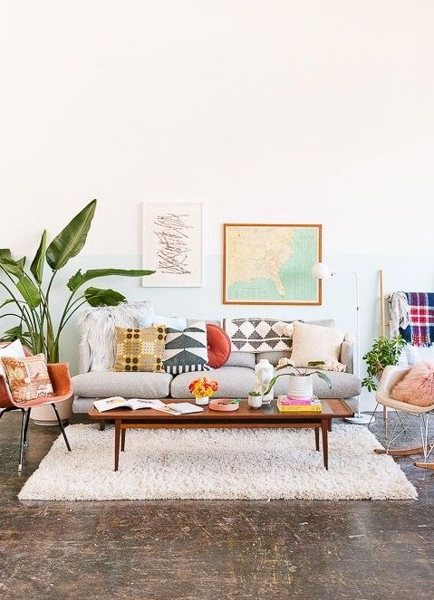 scandinavian living room with multicolors and graphic prints white shag rug mid century modern chairs tropical houseplant concrete floors
