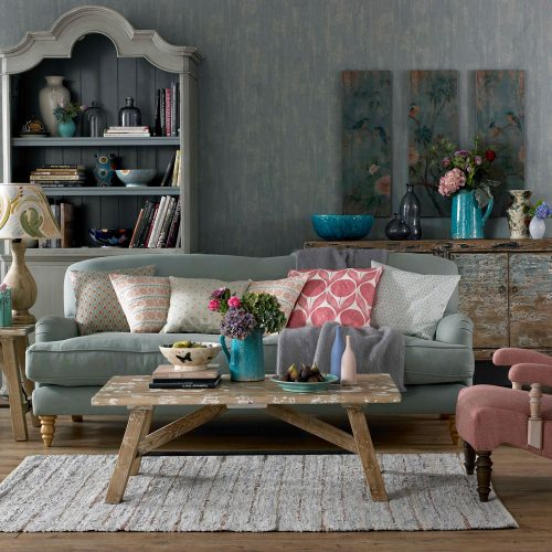 shabby chic living room soft blue upholstered sofa soft pink upholstered chair antique look area rug wood floors dusty blue wallpaper antique display unit