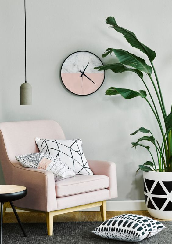 simple and small living room soft pink chair modern monochrome throw pillows houseplant with monochromatic pot pink white clock with black frame