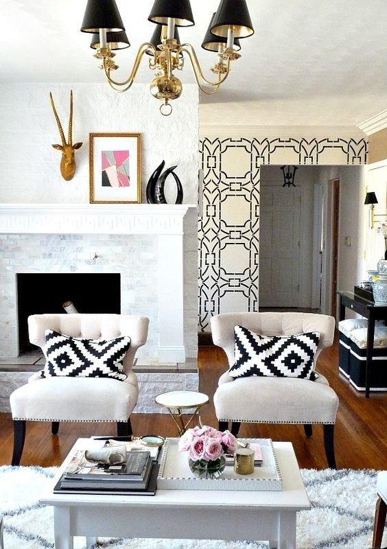 simple black and white living room traditional chairs in white white black throw pillows clean white coffee table white black wallpaper wood floors traditional chandeliers