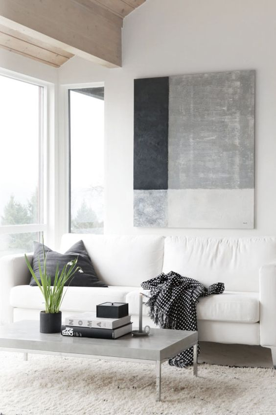 simple modern living room with accented modern abstract art white sofa black throw pillow light gray coffee table white shag rug