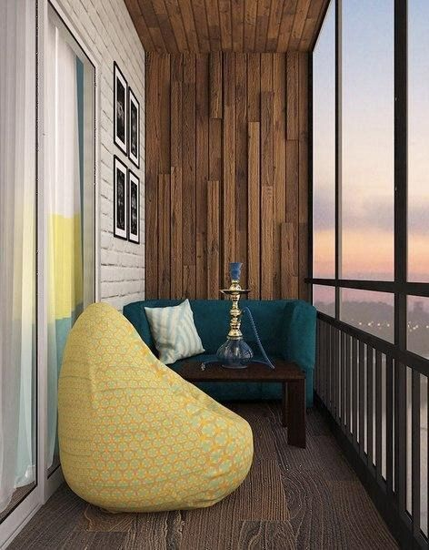 small enclosed balcony with seating nook dark blue couch throw pillow yellow bean bag dark coffee table dark wood floors textured wood slat wall wood railings with glass panel