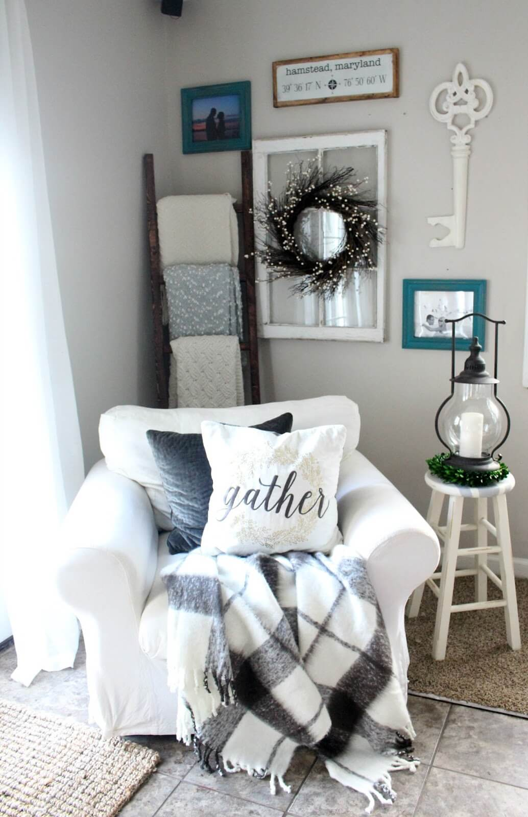 small living room in rustic farmhouse style white armchair monochrome blanket black and white throw pillows wood ladder rack white side table with round top wall decorations
