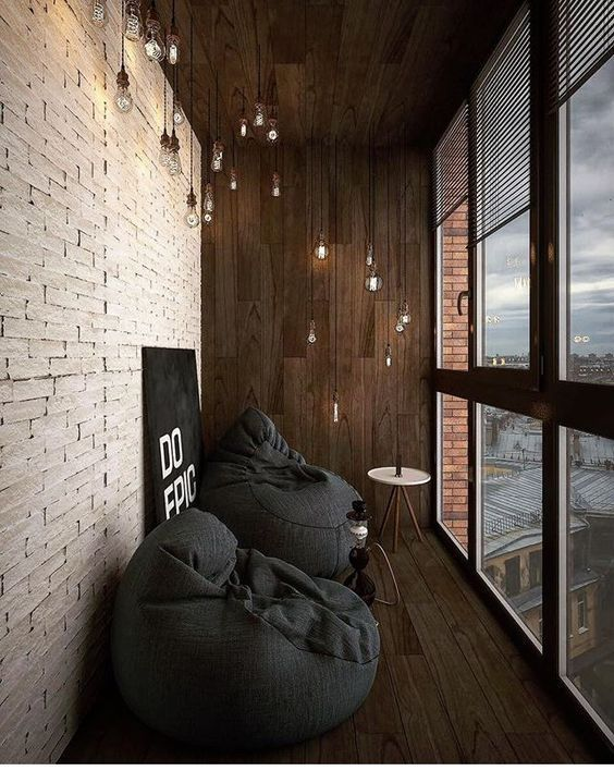 small seating nook in urban industrial style white brick walls old bulb lighting fixtures dark wood paneling floors and walls glass paneling with wood trims