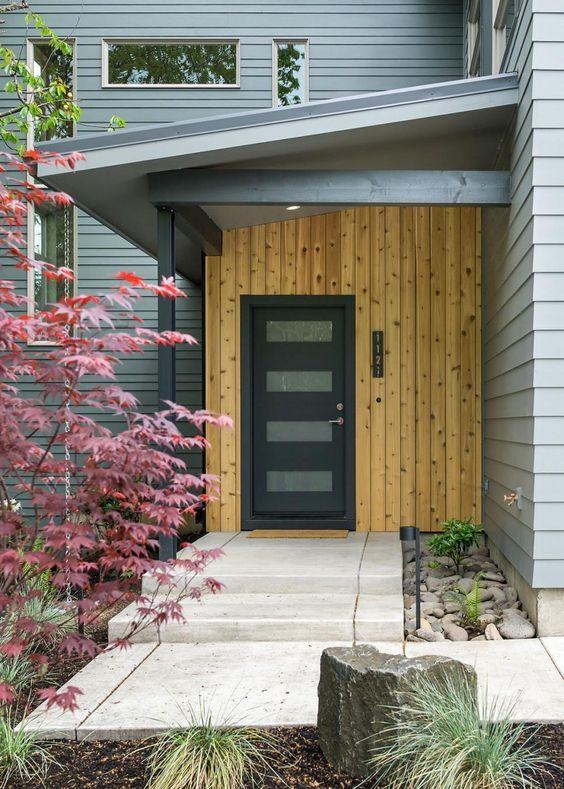 vertical wood board exterior wall gray metal front door concrete exterior floors