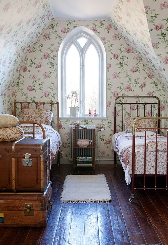 vintage style bedroom for twins flowery wallpapers centered window with curve top dark wood floors rustic suitcases white bed mat