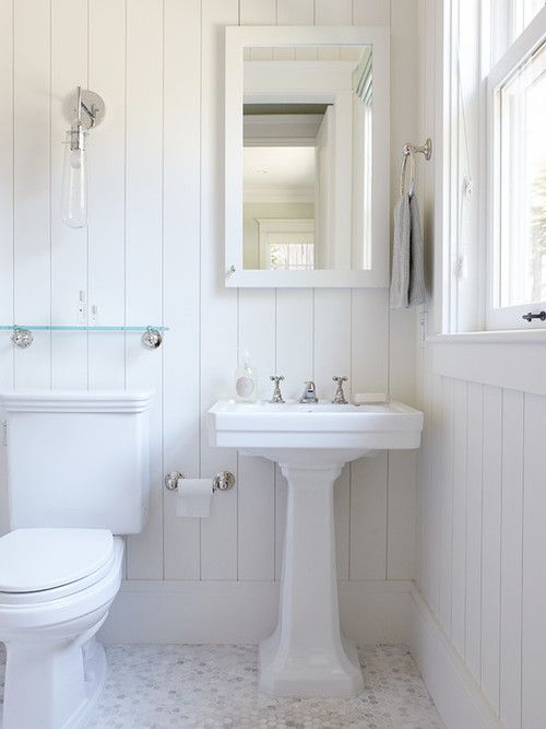 white pedestal sink white framed mirror white pallet walls white toilet