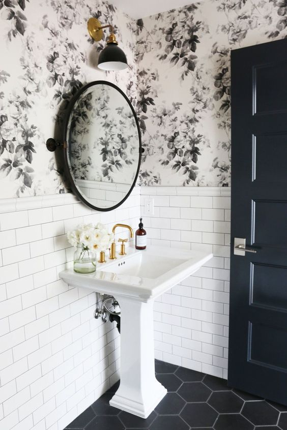 white pedestal sink with gold toned faucet black hexagon tiled floors white ceramic tiles walls black flower wallpapers