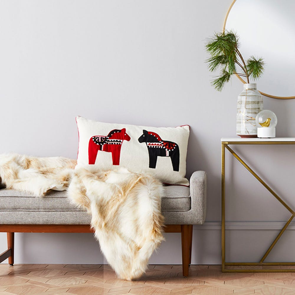 Hygge inspired seating area Scandinavian style bench with gray upholstery cream colored throw blanket
