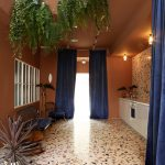 Mediterranean Style Hallway Idea Terrazzo Floors Blue Velvet Curtains Hanging Greenery White Counter A Couple Of Hall Chairs