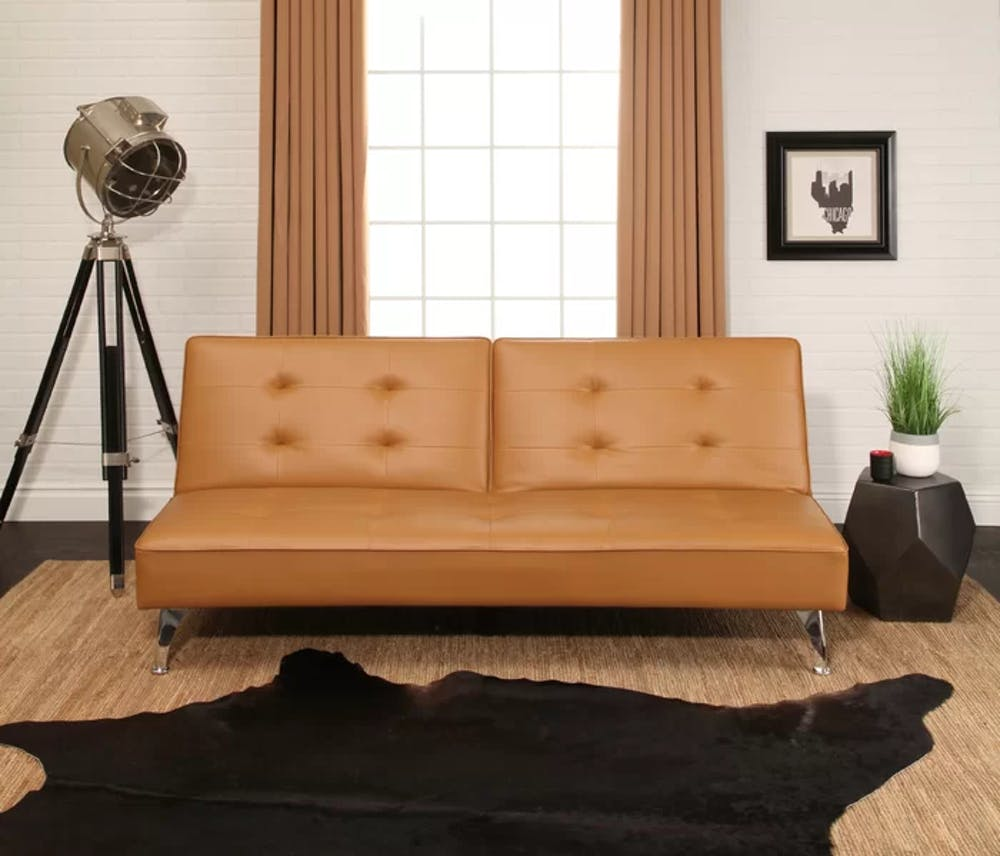 armless futon cushion with leather cover and agled chrome legs tripod floor lamp cowhide area rug in black