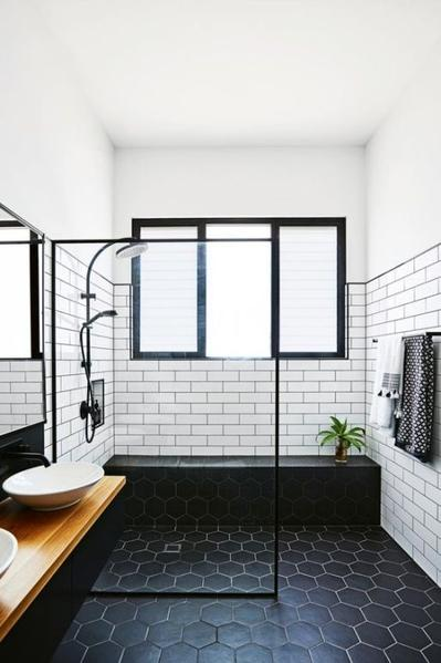 bathroom trend wood top floating bathroom vanity with a couple of white sink walk in shower space with glass panel white subway tile walls hexagone tile floors in black black shower bench