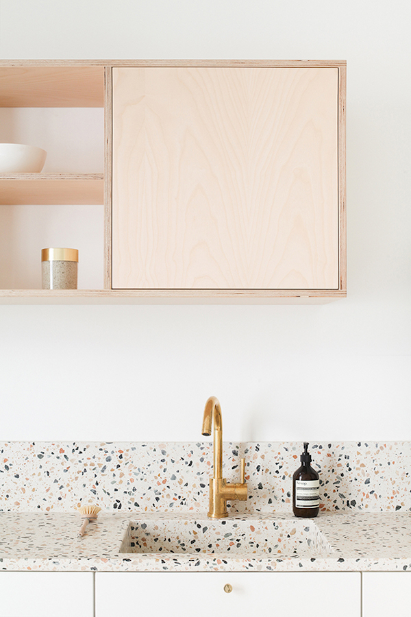 clean, bright, and light kitchen counter light pink cabinet terrazzo countertop gold toned faucet white wall