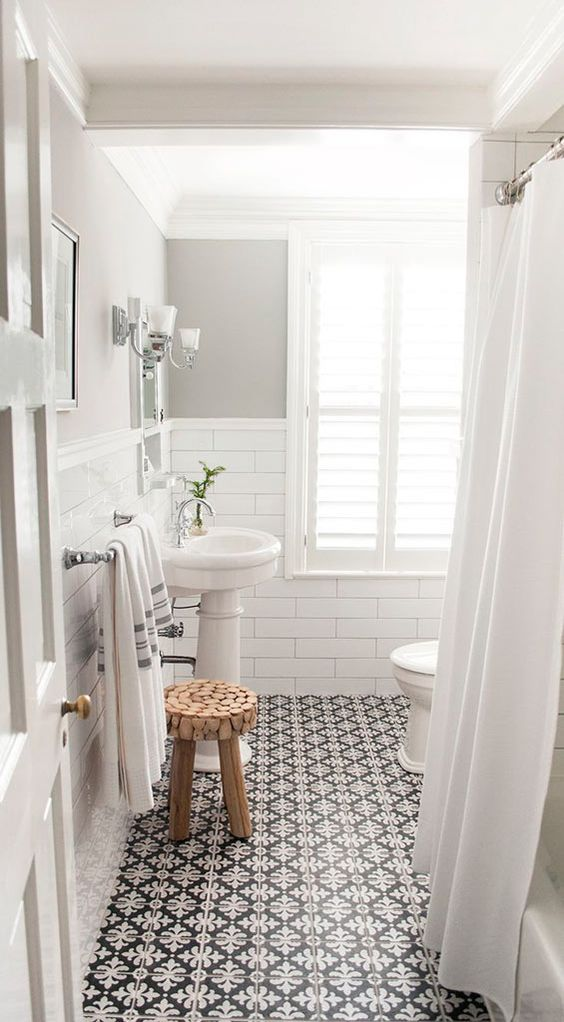 clean lined & modern bathroom design vintage tile floors with monochromatic patterns subway tile walls in gloss white dramatic white shower curtains