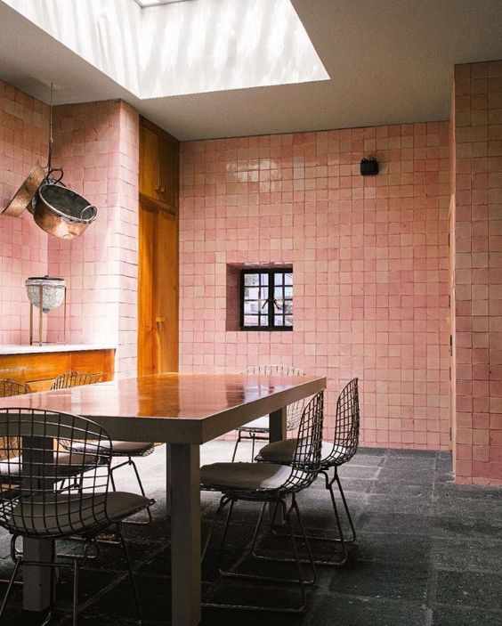 dining room blush pink tile walls hard textured natural stone block floors wood dining table modern dining chairs with stainless steel net back rest