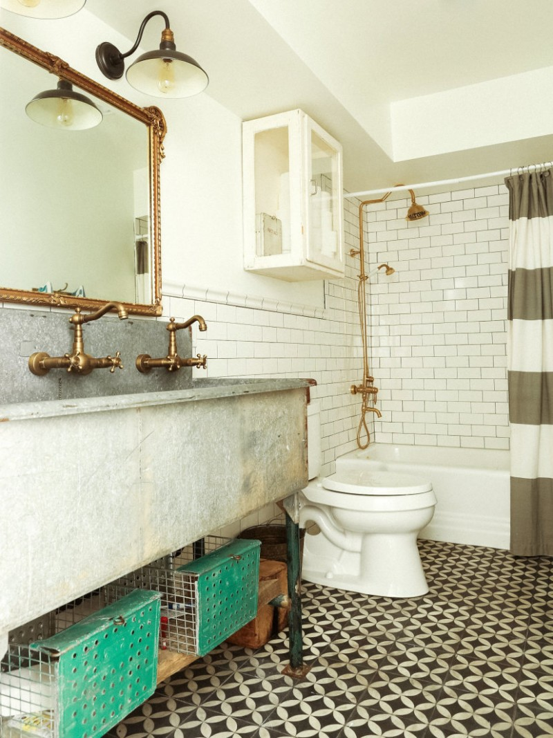 eclectic bathroom white subway tile walls white toilet extra large metal sink brass faucets brass framed vanity mirror mosaic tile floors